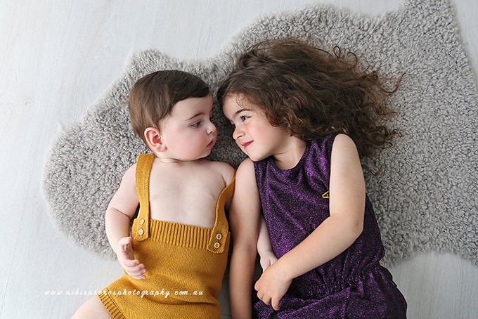 Baby brother lying next to sister